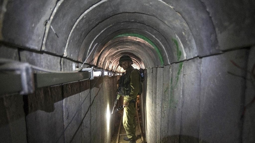 FILE - In this Friday, July 25, 2014 file photo, an Israeli army officer gives journalists a tour of a tunnel allegedly used by Palestinian militants for cross-border attacks, at the Israel-Gaza Border. Hamas is entering Egyptian-brokered talks with Israel over a new border regime for blockaded Gaza having lost hundreds of fighters, two-thirds of its arsenal of rockets, and its attack tunnels. (AP Photo/Jack Guez, Pool, File)