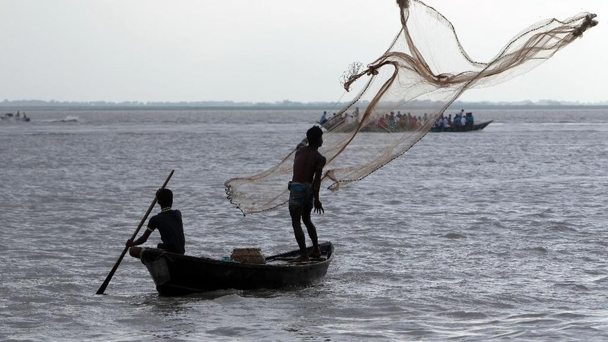 A Bangladeshi fisherman throws a fishing net as people gather on the banks of the River Padma where a passenger ferry capsized Monday in Munshiganj district, Bangladesh, Tuesday, Aug. 5, 2014. More than 200 people were believed to be on board the M.V. Pinak when it capsized Monday. Families of scores of people presumed dead accused authorities on Tuesday of launching a feeble rescue effort and leaving their loved ones trapped inside the vessel for more than 24 hours. (AP Photo/ A.M. Ahad)