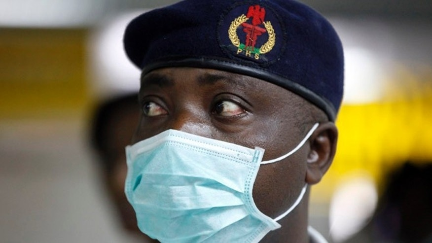 Aug. 4, 2014: A Nigerian health official wearing a protective mask waits to screen passengers at the arrivals hall of Murtala Muhammed International Airport in Lagos, Nigeria. Nigerian authorities on Monday confirmed a second case of Ebola in Africa's most populous country, an alarming setback as officials across the region battle to stop the spread of a disease that has killed more than 700 people.