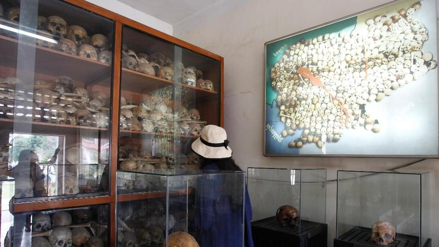 In this July 10, 2014 photo, a tourist looks at human skulls of genocide victims at the Tuol Sleng Genocide Museum, formerly the most notorious Khmer Rouge prison, in Phnom Penh, Cambodia. A U.N.-assisted court on Thursday, Aug. 7, 2014 will deliver its verdicts in a case against the two most senior surviving leaders of Cambodia's Khmer Rouge, charged with crimes against humanity. (AP Photo/Heng Sinith)