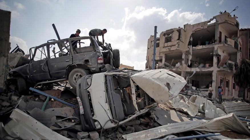Aug. 5, 2014: Palestinians search destroyed cars in Rafah's district of Shawkah in the southern Gaza Strip. The attack at the Shawkah district east of the Gaza town of Rafah drew what was by far the heaviest shelling by the Israeli military in the Gaza war, killing nearly 100 people that day alone and instantly unraveling a three-day ceasefire shortly after it came into force.
