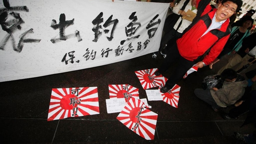 "FILE - In this April 19, 2012 file photo, an anti-Japan protesters stands on the Rising Sun Flags of the former Imperial Japanese military and shouts slogan ""Japan get out of Diaoyu Islands (Senkaku islands)"" during a demonstration near the Japanese Consulate in Hong Kong. Some place names don't just tell us where we live or where we're going. They're also a political statement, or in the eyes of some a politically incorrect one. They may not spark a war of the worlds, but a war of words they can. China struck back after Japan launched a verbal fusillade last week in August 2014, slapping monikers on 158 previously unnamed islands off its shores. Five of them are part of a cluster that the two both claim and is itself the subject of a name dispute. Is it the Senkaku or Diaoyu islands? (AP Photo/Kin Cheung, File)"