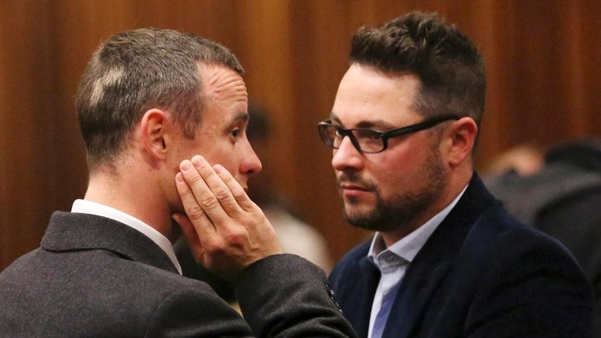 "FILE - In this Tuesday May 20, 2014 file photo brother of murder accused, Oscar Pistorius, left, Carl Pistorius, right, speaks with his brother in court in Pretoria, South Africa. Carl Pistorius has been ""badly hurt"" in a car accident after a head-on collision on a highway in South Africa, Friday, Aug. 1, 2014. (AP Photo/Siphiwe Sibeko, Pool, File)"