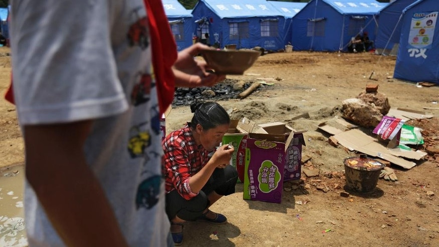 A woman eats instant noodle near the temporary tents set up for survivors of the earthquake in the town of Longtoushan in Ludian County in southwest China's Yunnan Province Wednesday, Aug. 6, 2014. The death toll in southern China's earthquake jumped to more than 500 on Wednesday as search and rescue teams found scores more bodies while pushing into isolated mountain communities to clear debris from collapsed homes. (AP Photo/Andy Wong)