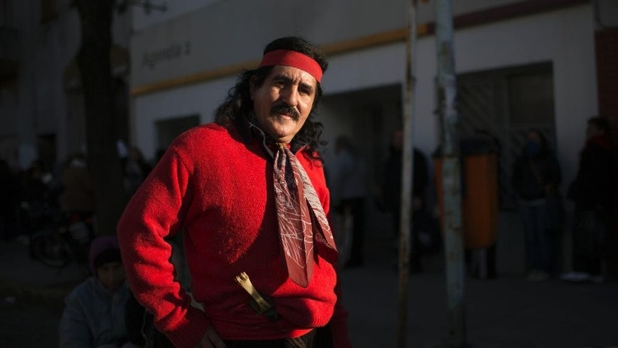 Angelito Ribero, poses for a photo dressed as 'Gauchito Gil,' a folk saint revered by Argentines, outside the San Cayetano church in Buenos Aires, Argentina, Thursday, Aug. 7, 2014. 'Gauchito Gil,' was an 1800's outlaw who became a mystical symbol of bravery; stealing from the rich and giving to the poor. Thousands of people visit the San Cayetano church, the patron saint of work, amid tough economic times in the South American country. (AP Photo/Natacha Pisarenko)