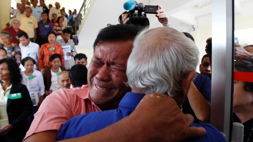 August 7, 2014: Cambodian former Khmer Rouge servitors, Soum Rithy, left, cries as he hugs Chum Mey, right, after the verdicts were announced, at the U.N.-backed war crimes tribunal in Phnom Penh. Three and a half decades after the genocidal rule of Cambodia's Khmer Rouge ended, the tribunal on Thursday sentenced two top leaders of the former regime to life in prison on war crimes charges for their role in the country's terror period in the 1970s. (AP Photo/Heng Sinith)