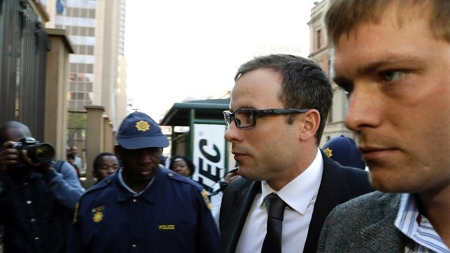 August 7, 2014: Oscar Pistorius, second from right, accompanied by a relative arrives at the high court in Pretoria, South Africa. (AP)
