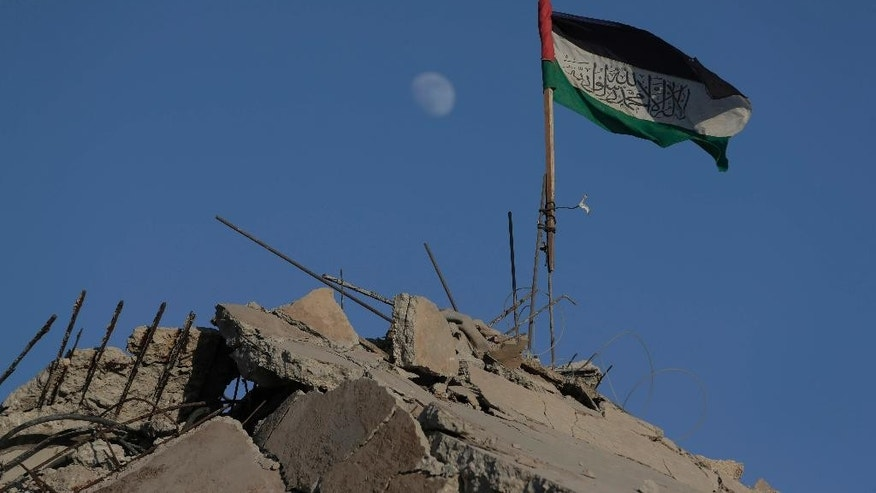 A Palestinian flag flies on the rubble of a house, destroyed by an Israeli strike in the Gaza City neighborhood of Shijaiyah, Gaza Strip, Thursday, Aug. 7, 2014. (AP Photo/Lefteris Pitarakis)