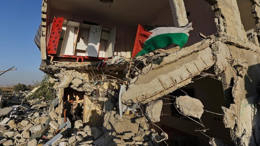 A Palestinian walks into a house, destroyed by an Israeli strike in the Gaza City neighborhood of Shijaiyah, Gaza Strip, as the national flag flies on the rubble, Thursday, Aug. 7, 2014. (AP Photo/Lefteris Pitarakis)