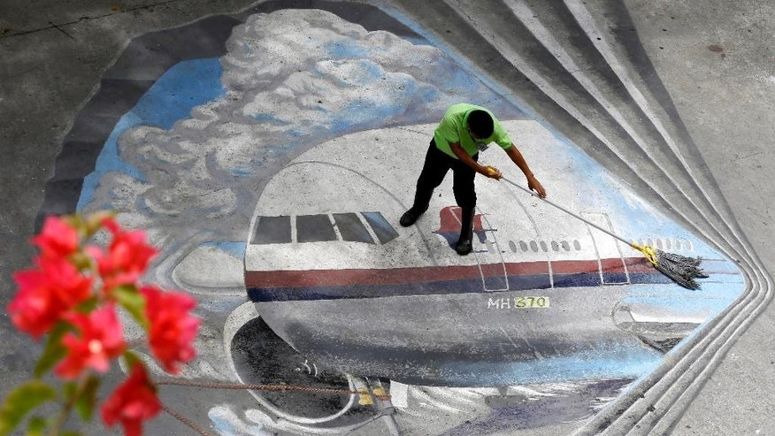 "FILE - In this April 8, 2014, file photo a school utility worker mops a mural depicting the missing Malaysia Airlines Flight 370 at the Benigno ""Ninoy"" Aquino High School campus at Makati city east of Manila, Philippines. Malaysia's state investment company said Friday, Aug. 8, 2014,  it plans to remove struggling Malaysia Airlines from the stock exchange, making it fully state-owned before a far-reaching overhaul of its business.(AP Photo/Bullit Marquez, File)"