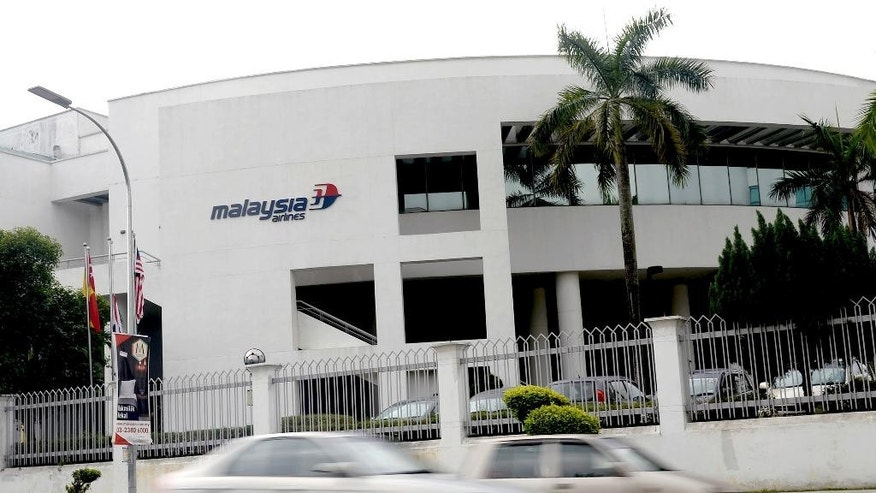 Cars drive past Malaysia Airlines Academy building in Kelana Jaya, near Kuala Lumpur, Malaysia, Friday, Aug. 8, 2014. Malaysia's state investment company said Friday it wants to remove struggling Malaysia Airlines from the stock exchange, making it fully state-owned before a far-reaching overhaul of its business. (AP Photo/Joshua Paul)