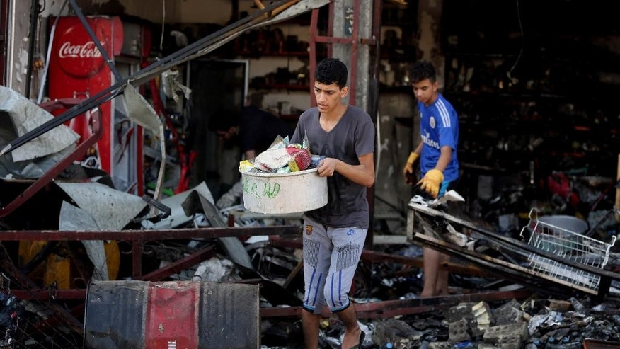 An Iraqi retrieves items from a destroyed shop the morning after a string of car bombs tore through busy shopping streets in several neighborhoods in Baghdad, Iraq, Thursday, Aug. 7, 2014. At least 50 people were killed on Wednesday as the army announced that one of its airstrikes had killed tens of militants in the northern city of Mosul. (AP Photo/Hadi Mizban)