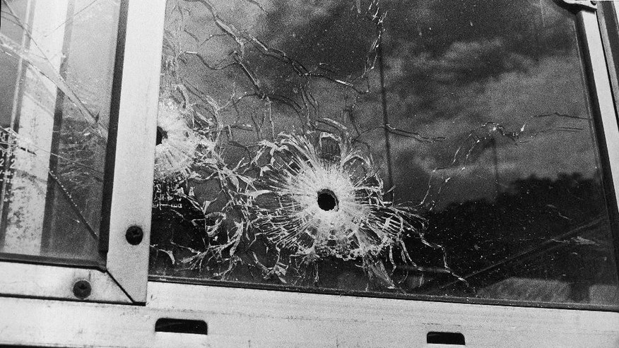 FILE - In this Dec. 3, 1979, file photo, large-caliber bullet holes pierce the driver's window of the U.S. Navy bus that was ambushed by terrorists in Puerto Rico. Federal authorities reopened the case after the Sept. 11 terror attack on the U.S. revived Washington's interest in suspected terrorists. Still, as the investigation dragged on, many people questioned whether it was worth the time and money, said Lou Eliopulos, director of NCIS's Office of Forensic Support. (AP Photo/FC,File)