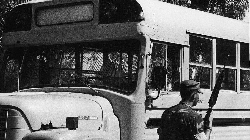 FILE In this Dec. 3, 1979, file photo, a U.S. Marine with an M-16 guards a U.S. Navy bus that was ambushed by Puerto Rican terrorist. Two sailors died and ten were wounded. The terrorist group, which is listed by the U.S. government as a terrorist organization, claimed responsibility for killings, bombings and robberies in the 1970s and '80s, including a $7 million holdup of a Wells Fargo depot in 1983. Its visibility diminished after a flurry of arrests in 1985.  (AP Photo/FC, File)