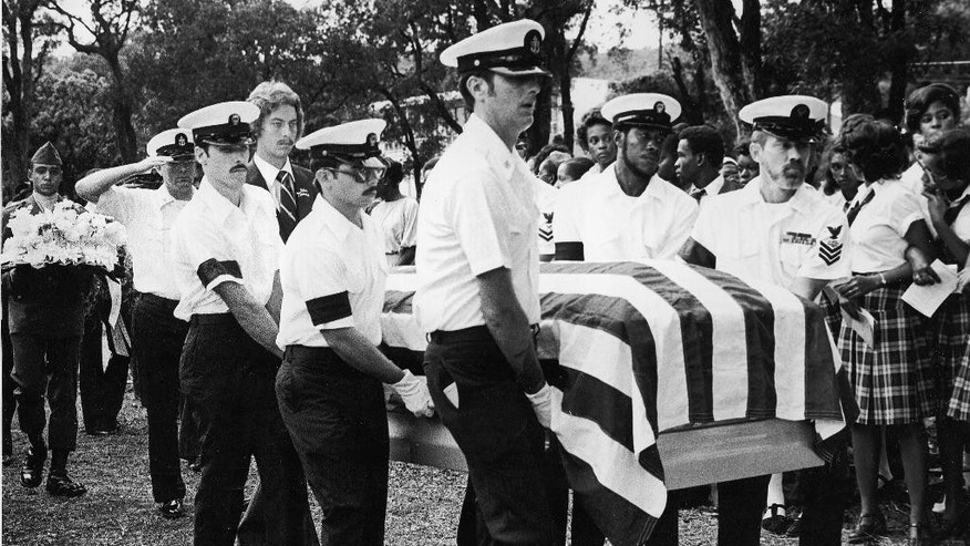 FILE- In this Dec. 9, 1979, file photo, an honor guard of the U.S. Navy carries the coffin bearing the remains of Radioman 3rd Class Emil E. White, one of two sailors killed in a terrorist attack on a Navy bus in Puerto Rico.  At one point, 13 people were suspected of involvement in the attack. Four of those have since died, including one suspected gunman whom authorities say died in a drug-related shooting. (AP Photo/HH, File)