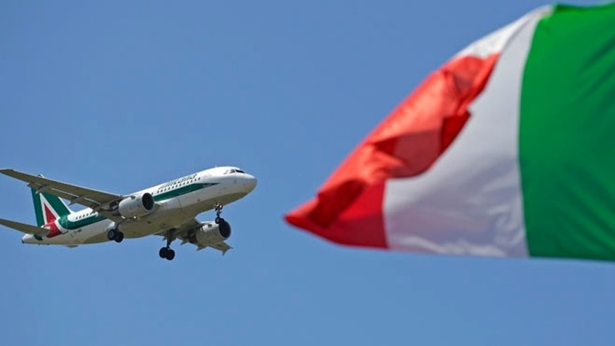 July 31, 2014: An Italy flag flutters as an Alitalia airplane approaches to land at Fiumicino airport in Rome.