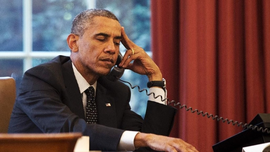 President Barack Obama listens during a phone call with Jordan's King Abdullah II Jordan, according to the White House, Friday, Aug. 8, 2014, in the Oval Office of the White House in Washington. (AP Photo/Jacquelyn Martin)