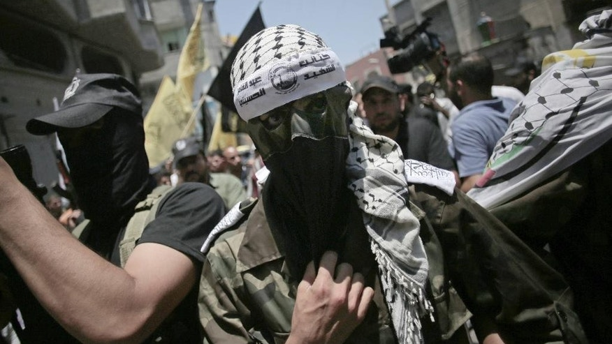 "FILE - In this file photo taken Monday, July 7, 2014, a masked militant wears a head band with Arabic writing that reads, ""the martyr, Abdul Qader Al-Husaini brigades,"" during the funeral of two Fatah militants, Marwan Sleem and Mazin Al-Jarba, who were killed by an Israeli airstrike, in Bureij refugee camp, central Gaza Strip. In the grisly math of the Israel-Hamas war, conflicting counts of combatants and civilians killed in Gaza are emerging - with the ratio perhaps more important to shaping international opinion of the monthlong conflict than any final toll. U.N. researchers and local rights groups say three-fourth of some 1,900 dead were civilians, while the Israeli military estimates the split is closer to 50-50. Those doing the tallies use different methods and standards to make that all important determination of who is a civilian. (AP Photo/Khalil Hamra, File)"