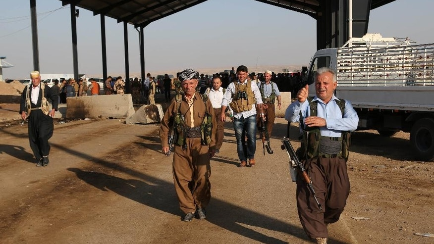 Kurdish Peshmerga fighters walk toward the front line with militants from the extremist Islamic State group, at the Khazer checkpoint outside of the city of Irbil in northern Iraq, Friday, Aug. 8, 2014. Iraqi Air Force has been carrying out strikes against the militants, and for the first time on Friday, U.S. war planes have directly targeted the extremist Islamic State group, which controls large areas of Syria and Iraq. (AP Photo/Khalid Mohammed)