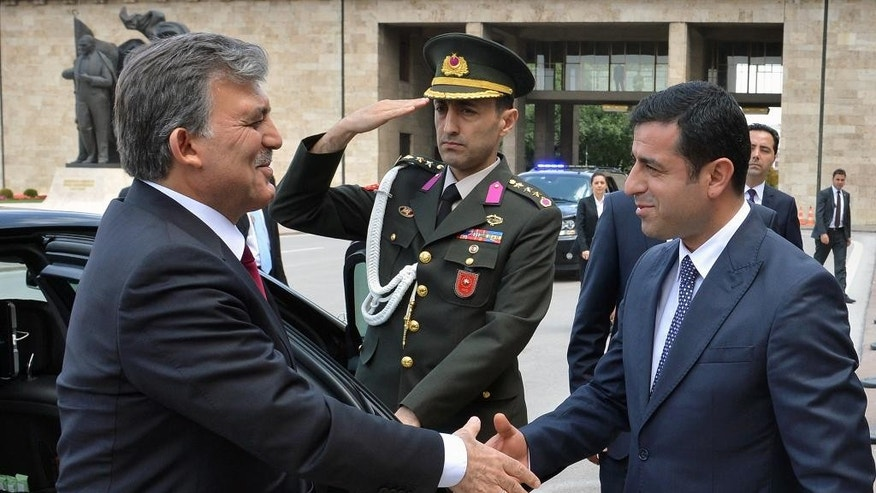 Turkish Kurdish presidential candidate for  Aug. 10 election, Selahattin Demirtas, right, welcomes Turkish President Abdullah Gul outside the parliament in Ankara, Turkey, Thursday, Aug. 7, 2014.  Prime Minister Recep Tayyip Erdogan is the unquestionable front-runner in Turkey's first direct presidential election on Sunday, and critics accuse him of using his position as premier to his advantage in the contest.(AP Photo)