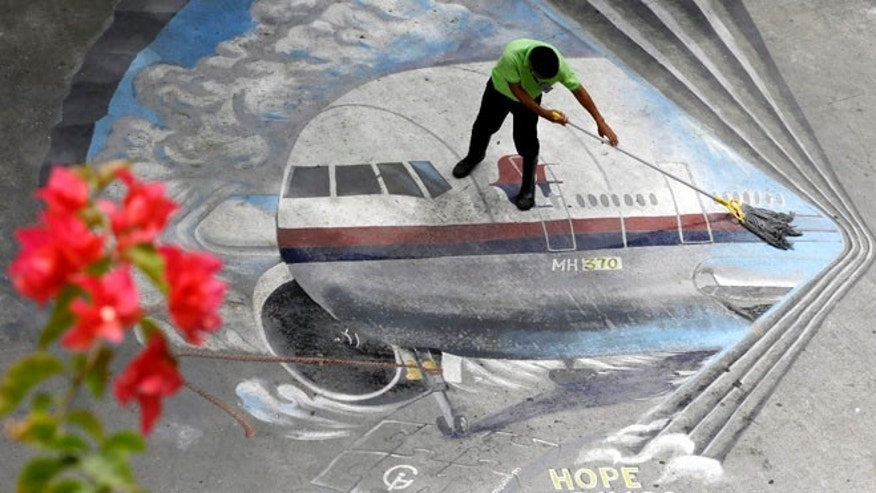 April 8, 2014: A school utility worker mops a mural depicting the missing Malaysia Airlines Flight 370 at the Benigno &quot&#x3b;Ninoy&quot&#x3b; Aquino High School campus at Makati city east of Manila, Philippines.