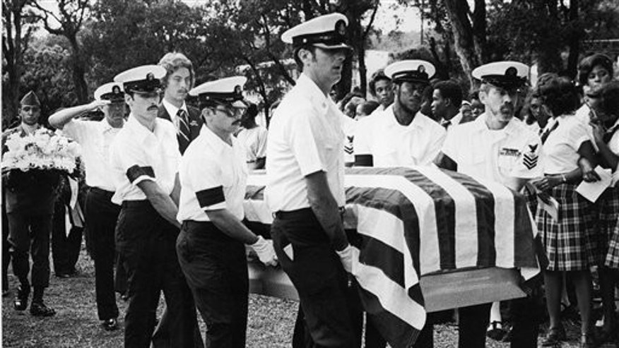 An honor guard carries the coffin bearing the remains of Radioman 3rd Class Emil E. White, on Dec. 9, 1979.