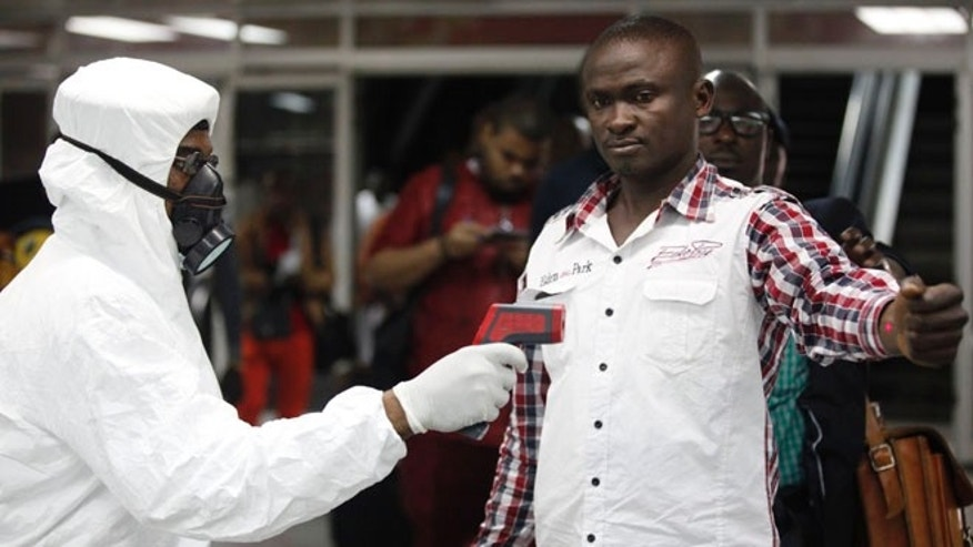 In this Aug. 6, 2014 file photo, a Nigerian port health official uses a thermometer on a worker at the arrivals hall of Murtala Muhammed International Airport in Lagos, Nigeria.