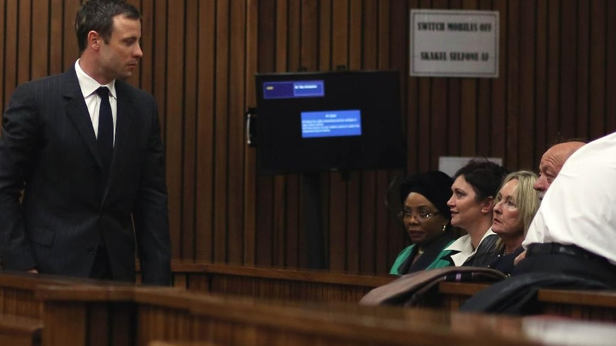 Oscar Pistorius, left, towards the parents of the late Reeva Steenkamp, June, second from right and Barry Steenkamp, right, on his arrival at court for his murder trial, in Pretoria, South Africa, Friday, Aug. 8, 2014. The chief defense lawyer for Oscar Pistorius delivered final arguments in the athlete's murder trial on Friday, alleging that Pistorius thought he was in danger when he killed girlfriend Reeva Steenkamp and also that police mishandled evidence at the house where the shooting happened. (AP Photo/ Themba Hadebe, Pool)