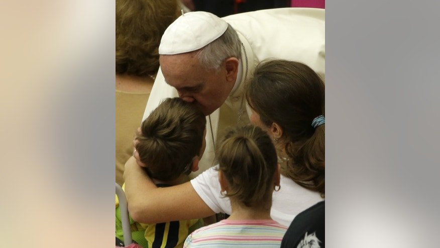Pope Francis kisses a child at the end of his weekly general audience in the Paul VI hall, at the Vatican, Wednesday, Aug. 6, 2014. (AP Photo/Andrew Medichini)