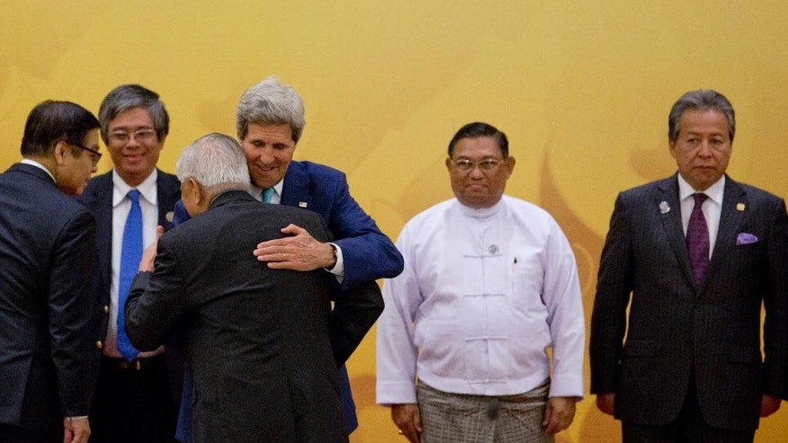 U.S. Secretary of State John Kerry, third right, hugs Philippines Foreign Minister Alberto del Rosario as Myanmar Foreign Minister Wunna Maung Lwin, second right, Malaysia Foreign Minister Anifah Aman, far right, and unidentified officials, left, watch upon Kerry's arrival for the ministerial meeting between the Association of Southeast Asian Nations (ASEAN) and U.S. in Naypyitaw, Myanmar, Saturday, Aug. 9, 2014. (AP Photo/Gemunu Amarasinghe)