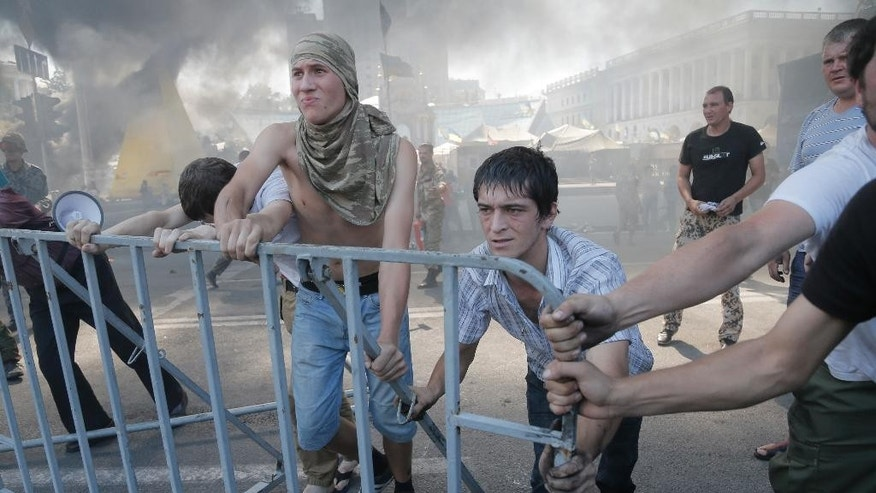 Activists build barricades during clash with a special forces police battalion, in Independence Square, Kiev, Ukraine, Thursday, Aug. 7, 2014. Demonstrators on Thursday confronted city workers attempting to clear a central square, lighting tyres on fire in protest against the city government's move. Dark plumes of smoke from burning rubber rose above Independence Square as workers guarded by armed men in camouflage dismantled some of the barricades surrounding the area. (AP Photo/Efrem Lukatsky)