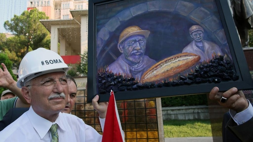The main opposition candidate in Turkey's Aug. 10 presidential election, Ekmeleddin Ihsanoglu, receives a painting depicting miners as he visits the monument of 301 miners killed in a mine catastrophe in May, in Soma, Turkey, Friday, Aug. 8, 2014. Some 53 million Turks go the polls on Sunday to choose their 12th president in an election considered a turning point for the country of 76 million people, with Prime Minister Recep Tayyip Erdogan vying for the position he has pledged to transform from a symbolic role into a position of power. Ekmeleddin Ihsanoglu, the former chief of the Organization of Islamic Cooperation, and Kurdish politician Selahattin Demirtas are also running. (AP Photo/Volkan Yildirim)