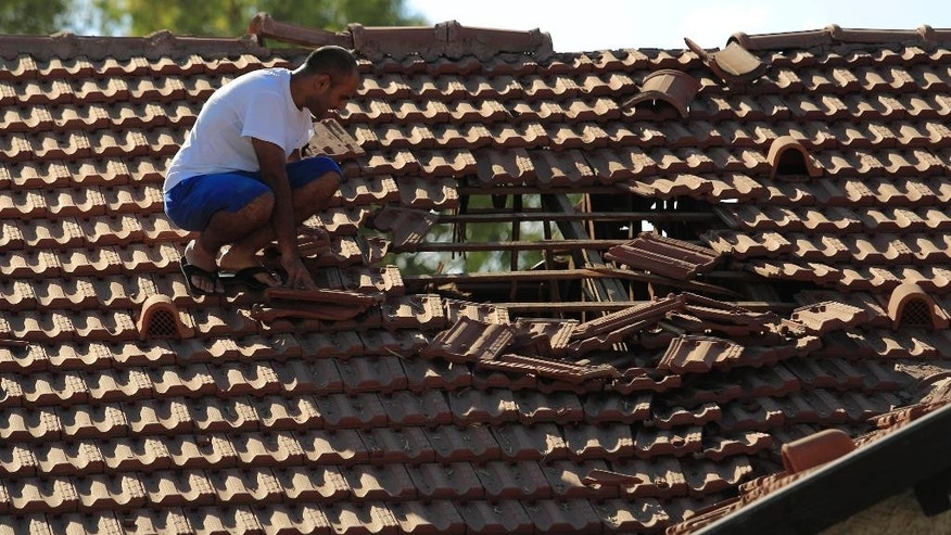 An Israeli man examines the damage to the roof of his house after a rocket fired from Gaza hit in a residential neighborhood of the southern city of Sderot, Israel, Friday, August 8, 2014. (AP Photo/Tsafrir Abayov)