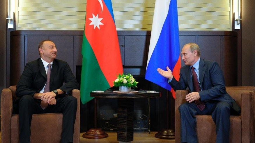 Russian President Vladimir Putin, left, gestures while speaking to Azerbaijani President Ilham Aliev prior to their talks in the Bocharov Ruchei residence in the Black Sea resort of Sochi, Russia, Saturday, Aug. 9, 2014. Presidents of Azerbaijan, Armenia and Russia meet in Sochi for their talks about Azerbaijan Armenia conflict. (AP Photo/RIA-Novosti, Presidential Press Service)