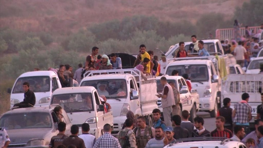 This image made from video taken on Sunday, Aug. 3, 2014 shows Iraqis people from the Yazidi community arriving in Irbil in northern Iraq after Islamic militants attacked the towns of Sinjar and Zunmar. Around 40 thousand people crossed the bridge of Shela in Fishkhabur into the Northern Kurdish Region of Iraq, after being given an ultimatum by Islamic militants to either convert to Islam, pay a security tax, leave their homes, or die. (AP Photo via AP video)