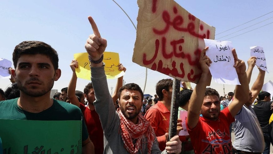 Iraqis from the Yazidi community chant anti Islamic militants slogans in front of UN headquarters to ask for international protection in Irbil, Iraq, Monday, Aug. 4, 2014. Islamic militants attacked the towns of Sinjar and Zunmar. Around 40 thousand people crossed the bridge of Shela in Fishkhabur into the Northern Kurdish Region of Iraq, after being given an ultimatum by Islamic militants to either convert to Islam, pay a security tax, leave their homes, or die. (AP Photo)