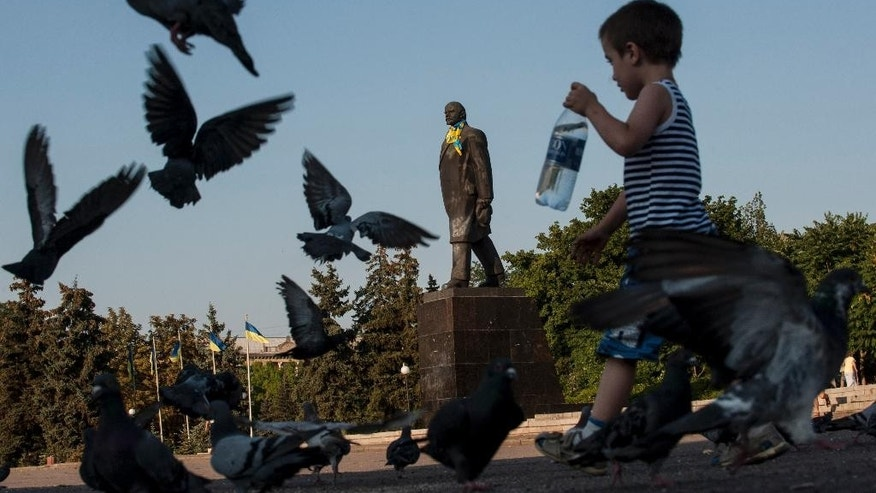 A Ukrainian boy walks past a statue of Soviet Union founder Vladimir Lenin decorated with a Ukrainian national flag in Kramatorsk, eastern Ukraine, Saturday, Aug. 9, 2014.(AP Photo/Evgeniy Maloletka)