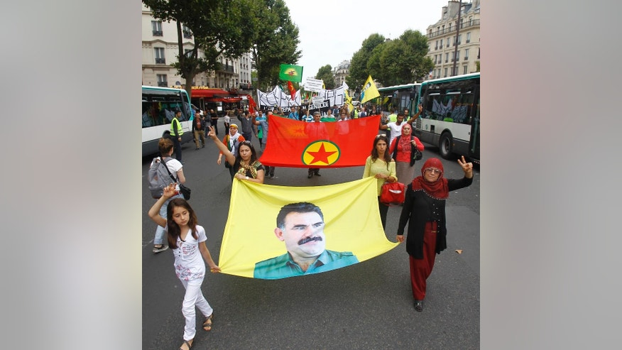 Kurdish demonstrators stage a protest in Paris, Saturday Aug. 9, 2014, in support of  Kurds and Christians living in Iraq.  Tens of thousands of Iraqi Christians and ethnic minorities are facing potential slaughter by Islamist militants in Iraq. Banner shows a portrait of PKK founder Abdullah Ocalan. (AP Photo/Remy de la Mauviniere)