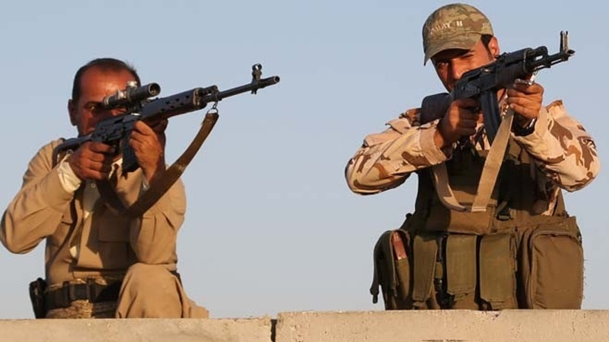 FILE: Aug. 8, 2014: Kurdish Peshmerga fighters during airstrikes targeting Islamic State militants outside of the city of Irbil in northern Iraq.