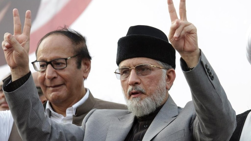 Pakistani Muslim cleric Tahir-ul-Qadri, flashes the victory sign to his supporters, in Lahore, Pakistan, Sunday, Aug. 10, 2014. Fighting between Pakistani security forces and supporters of a fiery anti-government cleric, Tahir-ul-Qadri, killed seven people as they were heading towards a planned demonstration in the city Lahore, the cleric claimed Saturday. Authorities have contested the cleric's claim and put the death toll from clashes at two, including one police officer. (AP Photo/K.M. Chaudary)