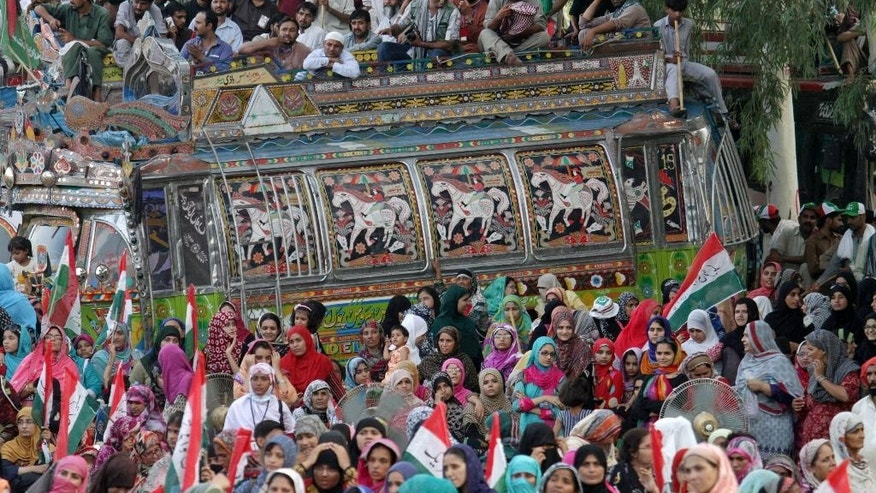 Supporters of Pakistani cleric Tahir-ul-Qadri listen to him speak around and atop an intricately decoorated bus at a rally in Lahore, Pakistan, Sunday, Aug. 10, 2014. Fighting between Pakistani security forces and supporters of a fiery anti-government cleric, Tahir-ul-Qadri, killed seven people as they were heading towards a planned demonstration in the city Lahore, the cleric claimed Saturday. Authorities have contested the cleric's claim and put the death toll from clashes at two, including one police officer. (AP Photo/K.M. Chaudary)