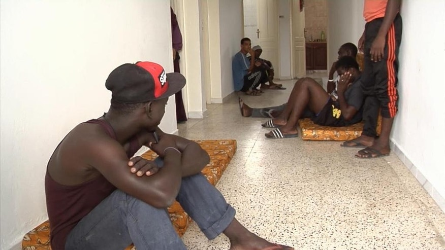 In this image taken from TV in  African migrants sit in a corridor at the Red Crescent centre in Zarzis Tunisia Monday Aug. 5, 2014.  Zarzis is like many other costal towns in Tunisia, it relies heavily on it's fishing industry, which employs many of the local men. The fishermen are netting a catch of a different kind too - migrants who attempt to cross the waters, trying to get in to Europe by sea. Many of these migrants have their sights set on a better life, fleeing conflicts in their home countries. (AP Photo/Associated Press Television)