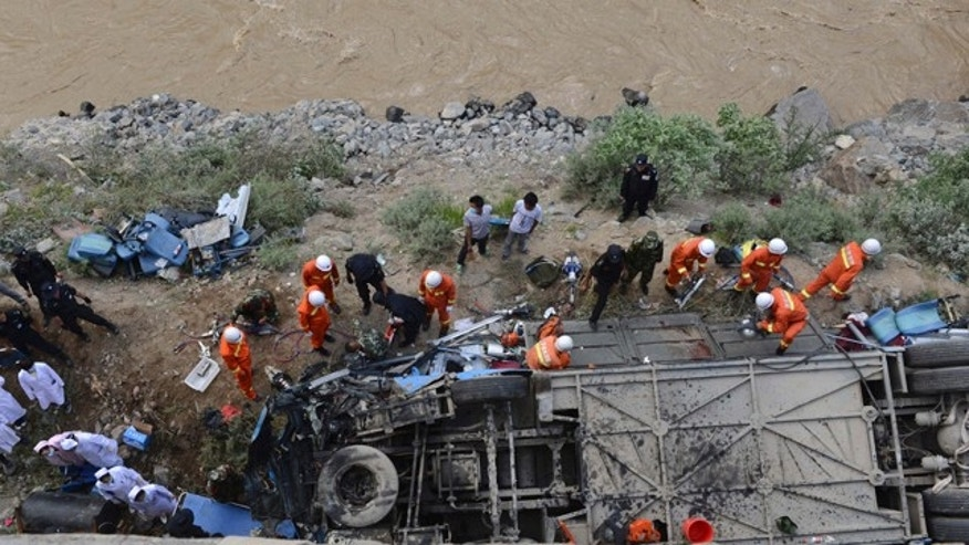 August 9, 2014: In this photo released by China's Xinhua News Agency, rescuers work around an overturned tour bus after it fell off a 30-foot cliff in Nyemo County in southwest China's mountainous region of Tibet. (AP Photo/Xinhua, Chogo).