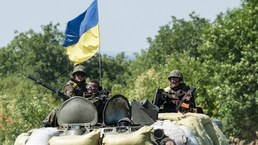August 9, 2014: Ukrainian government troops sit atop of their military vehicle in Donetsk region. (AP Photo/Evgeniy Maloletka)