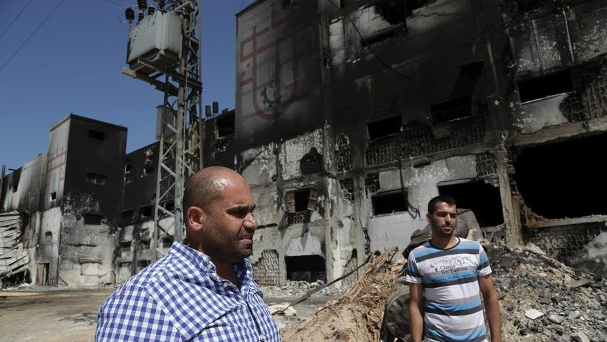 In this Sunday, Aug. 10, 2014 photo, Ibrahim al-Telbani, left, and Ahmad Baraka inspect the damaged and burned Al Awda snack food factory in Deir el-Balah, central Gaza Strip. Factory owner, Mohammed al-Telbani, lost his life's work during the Gaza war after Israeli shells slammed into his four-story factory, one of Gaza's largest, sparking a fire that engulfed vats of margarine and sacks of cocoa powder. Al-Telbani and others in Gaza say anything short of a complete opening of Gaza's borders, after seven years of closure by Israel and Egypt, will do little to change their lives. (AP Photo/Adel Hana)