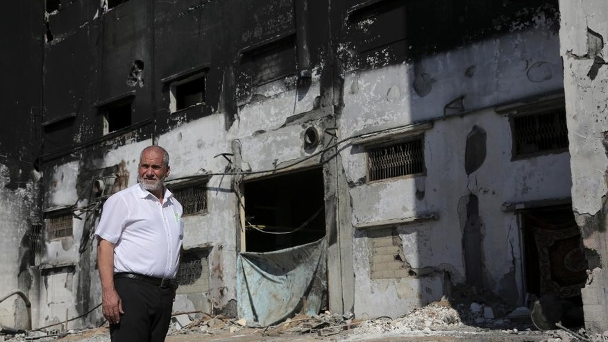 In this Sunday, Aug. 10, 2014 photo, Mohammed al-Telbani, owner of Al Awda snack food  factory, poses in front of his burned factory in Deir el-Balah, central Gaza Strip. Al-Telbani lost his life's work during the Gaza war after Israeli shells slammed into his four-story factory, one of Gaza's largest, sparking a fire that engulfed vats of margarine and sacks of cocoa powder. Al-Telbani and others in Gaza say anything short of a complete opening of Gaza's borders, after seven years of closure by Israel and Egypt, will do little to change their lives. (AP Photo/Adel Hana)