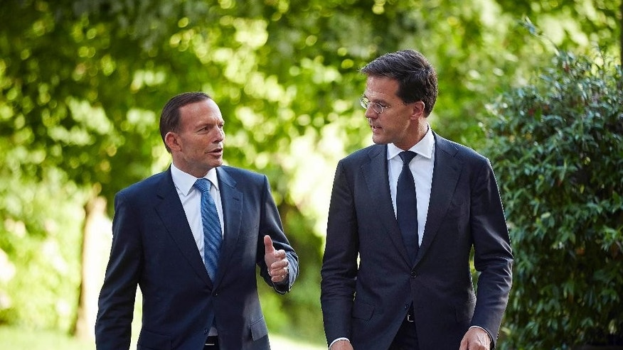 Dutch Prime Minister Mark Rutte, right, and Australian Prime Minister Tony Abbott, left, speak as they walk to a press conference in The Hague, Netherlands, Monday, Aug. 11, 2014. Abbott and Rutte met Monday to discuss repatriation of Australian victims of the Malaysia Airlines Flight 17 disaster and to examine possibilities for prosecuting the persons responsible for downing the civilian plane in eastern Ukraine on July 17. (AP Photo/Phil Nijhuis)