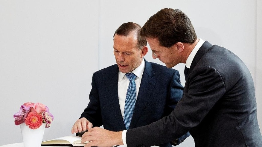 Australian Prime Minister Tony Abbott, left, signs a book of condolence as Dutch Prime Minister Mark Rutte, right, looks on after their meeting in The Hague, Netherlands, Monday, Aug. 11, 2014. Abbott and Rutte met Monday to discuss repatriation of Australian victims of the Malaysia Airlines Flight 17 disaster and to examine possibilities for prosecuting the persons responsible for downing the civilian plane in eastern Ukraine on July 17. (AP Photo/Martijn Beekman, Pool)