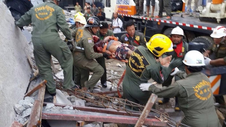 Rescue workers carry a survivor from the rubble of a collapsed building in Pathumthani province, central Thailand Monday, Aug. 11, 2014. A six-story building under construction on the outskirts of Thailand's capital collapsed Monday, killing  a number of workers and trapping others underneath the rubble, police said. (AP Photo) THAILAND OUT