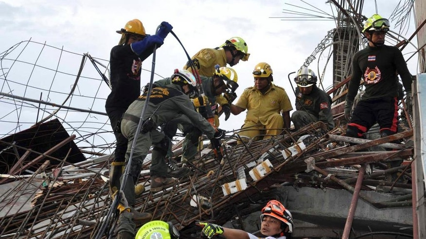 Police and rescue workers search through the rubble of a collapsed building in Pathumthani province, central Thailand, Monday, Aug. 11, 2014. A six-story building under construction on the outskirts of Thailand's capital collapsed Monday, killing a number of workers and trapping several others underneath the rubble, police said. (AP Photo) THAILAND OUT